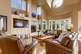 Large living room interior design with high vaulted ceiling and leather sofa set.