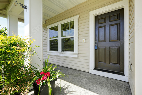 Poster Open porch with concrete floor, column and entrance brown door.