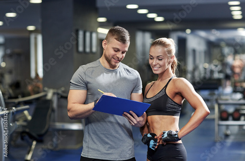 obraz lub plakat smiling young woman with personal trainer in gym