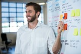 Smiling businessman pointing on sticky note
