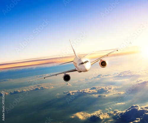 Fototapeta Airplane flying above clouds in dramatic sunset