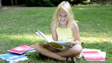 little cute smart girl sits in the park with many workbooks - she enjoy the study