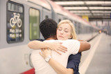 Interracial couple hugging at the train station