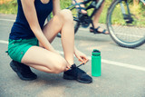 Female athlete, tying sport footwear laces on road before training