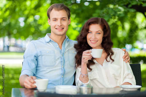 Poster Happy couple drinking a cappuccino outdoors