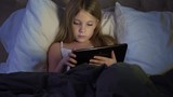 Young child at night with tablet in bed on the internet.