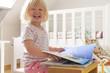 Kleinkind im Kinderzimmer schaut lachend ein Buch an.