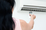 Woman turns on air conditioning in a room - 115389440