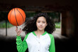 Portrait of a young brunette with a basketball in the street