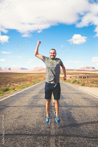 Poster Young man jumping in the middle of the Monument Valley road