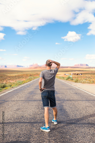 Poster Young man standing in the middle of the Monument Valley road