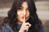 Portrait of beautiful woman with finger on lips.