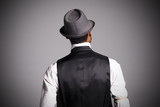 Hombre con chaleco y sombrero de espaldas