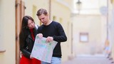 Happy tourist couple traveling on holidays in Europe smiling happy. Caucasian couple with citymap outdoors
