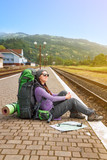 Girl with backpack and map waiting train at the railway station