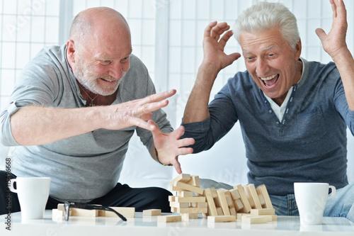 Poster senior men playing  board game