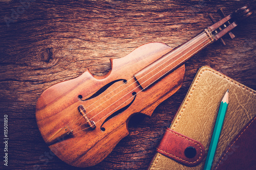 obraz lub plakat Violin and notebook with pencil on grunge dark wood background