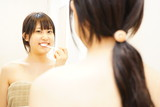 歯磨きをする日本人の若い女性 / Young japanese woman brushing her teeth in a bathroom