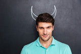 Closeup of handsome young man with drawn devil horns