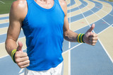 Athlete with Brazil colors yellow and green wristband giving thumbs up in front of the running track