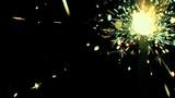 Burning green and orange sparkler against black background 4K video