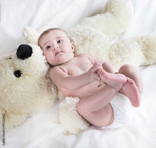 obraz PCV .The baby is playing with bear in yellow