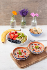 Vegan fruit and berry smoothie breakfast, topped with blueberries, strawberries and mint, seved with fruits, berries and nuts, selective focus