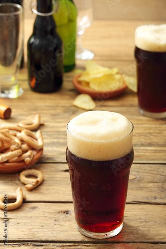 Poster bicchiere di  birra scura su sfondo tavolo di legno rustico