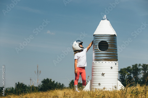 Happy child girl dressed in an astronaut costume playing with hand made rocket. Summer outdoor