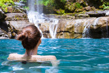 Fototapety Beautiful woman enjoying bathing near natural waterfall.