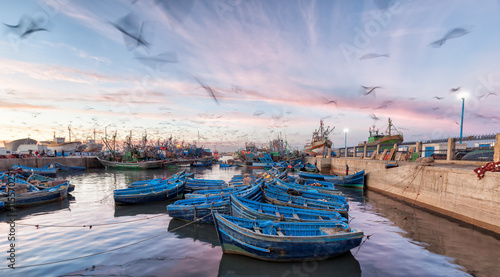 Morocco waterfront at sunset with motion blur of seagulls flying over blue boats
