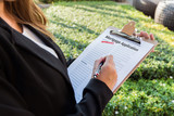 Businesswoman signing approved mortgage application in the garden