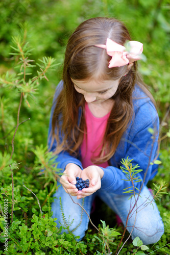 Cute little girl picking blueberries in the woods