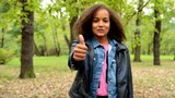 young african happy girl with fluffy afro shows thumb up in the park - eye contact - agree