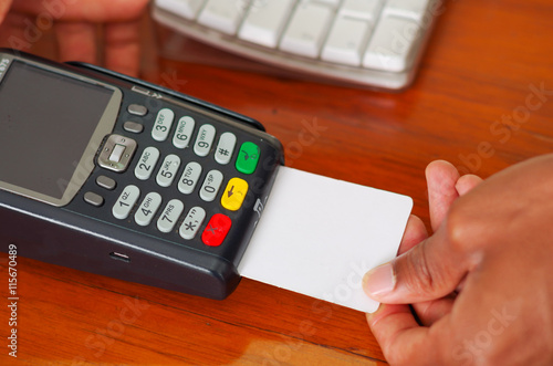 Closeup hands prcessing payment using credit card terminal device sitting on wooden surface, seen from above angle