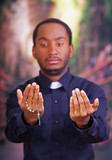 Catholic priest wearing traditional clerical collar shirt standing facing camera, holding hands out with rosary cross, looking forward, religion concept