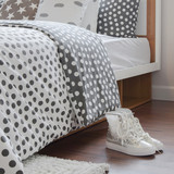 modern bedroom interior with girl sneaker on wooden floor and polka dot bedding