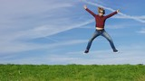 4K Happy man jumping for joy on grass, in slow motion, with space for text