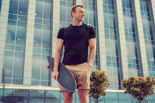 mata magnetyczna Casual urban male holding longboard.