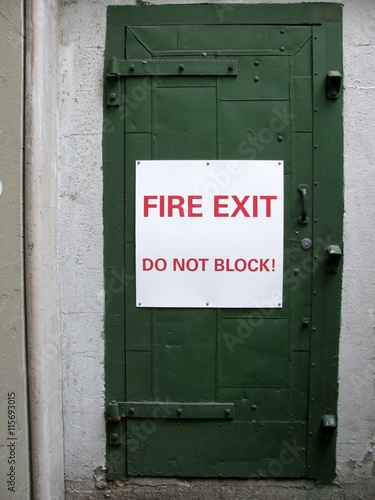 Poster Fire exit do not block! sign on a green door