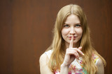Young beautiful blonde woman has put forefinger to lips as sign