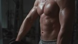 Tilt up of young sexy sportsman doing dumbbell front raise in the gym in slow motion