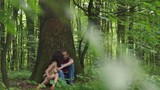 Young happy loving couple sitting at the tree with heart carved on it and kissing. Green spring forest background