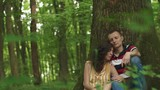 Beautiful loving couple sitting with eyes closed at the tree with heart carved on it and relaxing. Green spring forest background