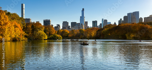 Fall in Central Park at The Lake with Midtown Manhattan skyscrapers. Panoramic afternoon cityscape view with colorful fall foliage. Manhattan, New York City