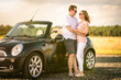 Liebespaar steht vor einem Cabrio - Mann und Frau umarmen sich vor einem Auto