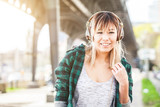 Portrait of a beautiful young woman in Hamburg listening music. She is Japanese, on her early twenties, brunette, wearing big headphones and listening music, looking at camera and smiling.