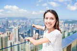 Woman finger pointing down to the city of Hong Kong