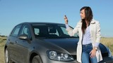 young attractive happy woman holds key of new car - she is absolutely satisfied - she stands by the new car - eye contact