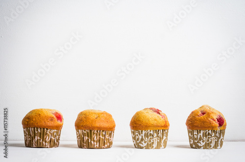Poster Homemade muffins with strawberries on the wooden background